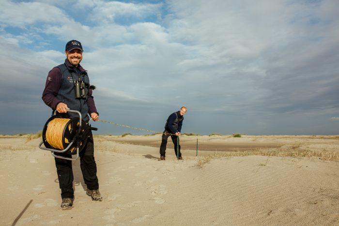 Nationalpark-Ranger installieren einen Schutzzaun für ein Brutgebiet am Borkumer Strand.
